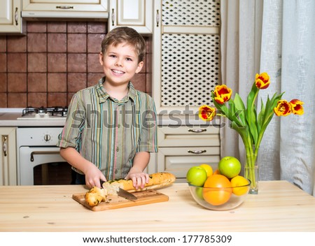 Smiling boy cutting a slice of bread. Mother's day.