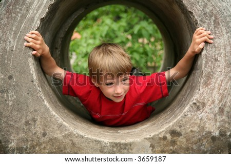 smiling boy hiding in a tunnel