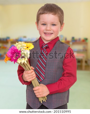 Smiling boy in a tie with a bouquet of flowers.child, happiness and people concept, lovely smiling toddler portrait