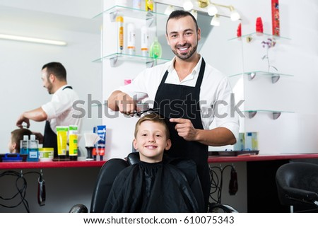 Smiling boy in elementary school age getting hairstyle of man hairdresser in beauty salon