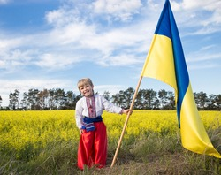Smiling boy in national Ukrainian clothes with yellow - blue large flag in hand against background of blooming rapeseed field. pride, symbol of country, nationality of Ukraine. Patriotic education.