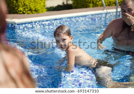 Smiling boy in the swimming pool. Family in the swimming pool. Family Vocation  #693147310