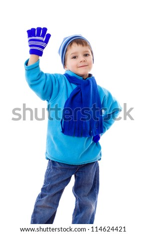 Smiling boy in winter clothes with greeting sign, isolated on white