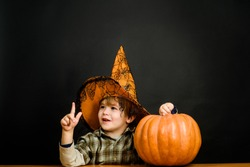 Smiling boy in witch hat with halloween pumpkin. Kid with pumpkin. Halloween holidays. Trick or treat. Halloween boy pointing finger up. Halloween costume. Funny Pumpkin. Celebration party. 31October.