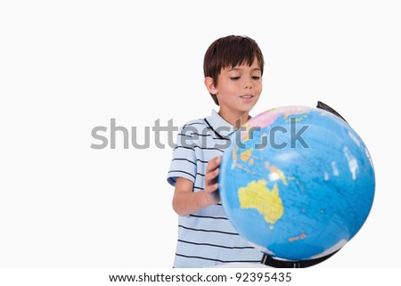 Smiling boy looking at a globe against a white background