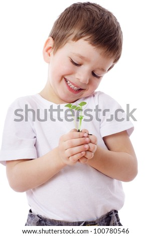 Smiling boy looking to sprouts in hands, isolated on white