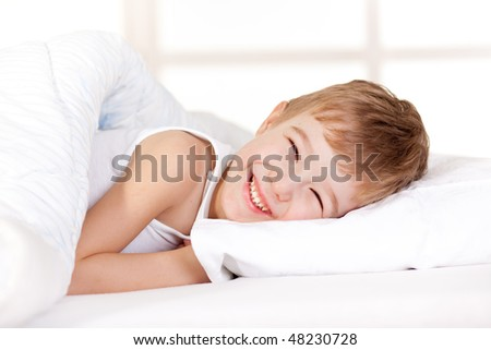 stock-photo-smiling-boy-on-the-bed-48230728.jpg