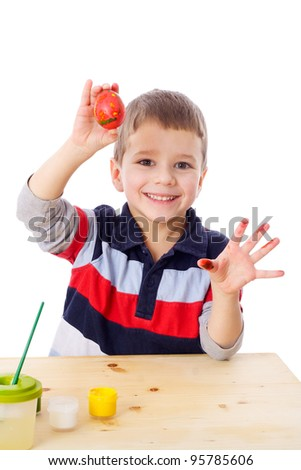 Smiling boy showing painted easter egg, isolated on white