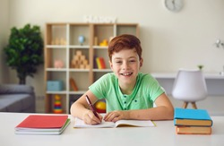 Smiling boy sitting at desk with notebooks and textbooks, doing homework and looking at camera over room interior background. Education online, children classes and funny studying concept