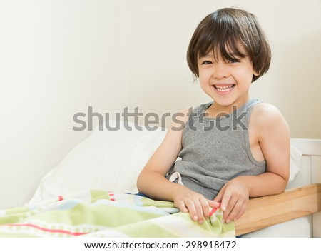Smiling boy sitting in bed. Little boy going to bed. Happy Child at bedtime. Boy in gray tank top pajamas ready to sleep. A toddler bed with young brown haired boy sitting in it. Bedtime at home