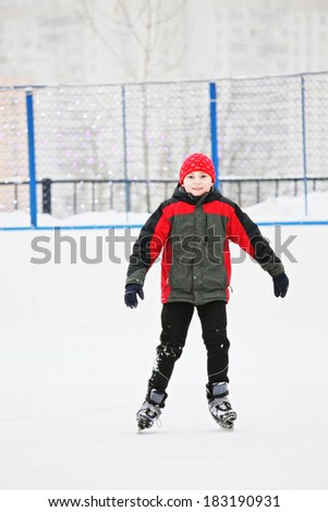 Smiling boy standing on the ice rink outdoors