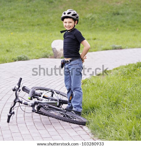Smiling boy standing over bike in park