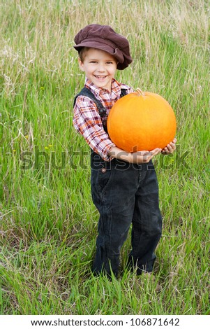 Smiling boy standing with big yellow pumpkin in hands