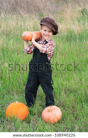 Smiling boy standing with pumpkins in the field