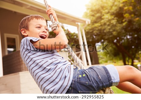 Smiling boy swinging on a rope at a playground