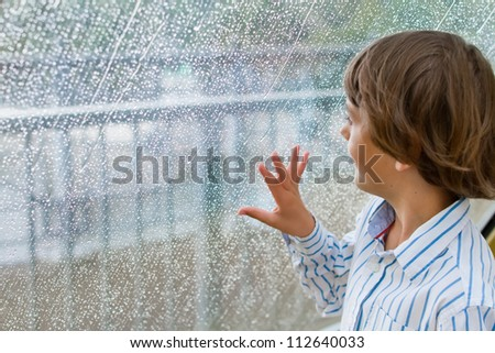 Smiling boy watching the rain outside at a window