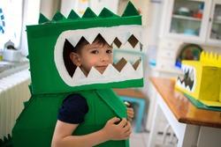 Smiling boy wearing a cardboard dinosaur costume