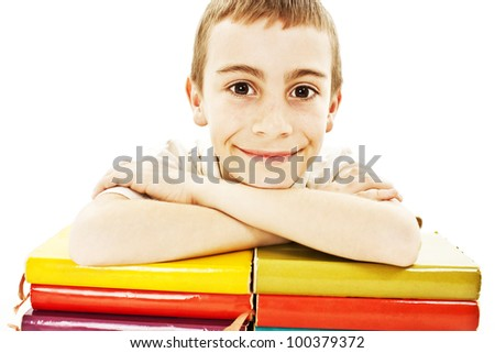 Smiling boy with colored school books on the table.  Isolated on white background.