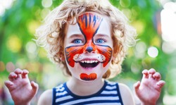 smiling boy with curly hair and face art painting like tiger, little boy making face painting, halloween party, child with funny face painting, boy with face art on birthday party close up