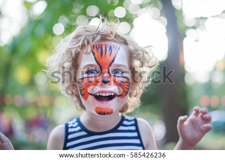smiling boy with curly hair and face art painting like tiger, little boy making face painting, halloween party, child with funny face painting, little cute boy with faceart on birthday party close up #585426236