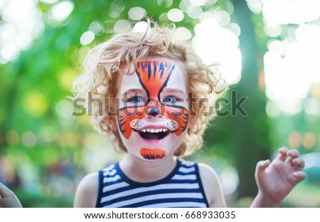 smiling boy with curly hair and face art painting like tiger, little boy making face painting, halloween party, child with funny face painting, little cute boy with faceart on birthday party close up  #668933035