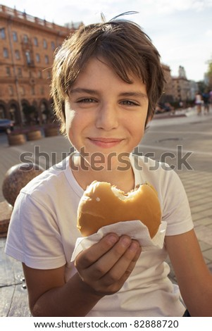 smiling boy with hamburger on city street
