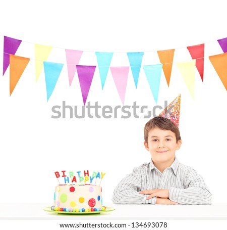 Smiling boy with party hat and a birthday cake isolated against white background
