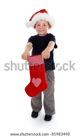 Smiling boy with Santa hat holding red Christmas stocking in front of him with both hands