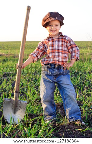 Smiling boy with shovel in field