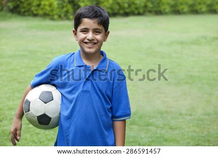 Smiling boy with soccer ball in park