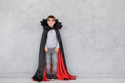 Smiling boy with vampire makeup and black, red cloak with bat like collar on a gray textured background. Halloween mood, copy space available. Cute kid wearing halloween costume.
