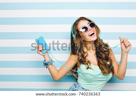 Smiling brown-haired girl enjoying favorite song and dancing in turquoise tank-top. Close-up indoor portrait of excited curly young woman having fun in headphones with phone on striped background.