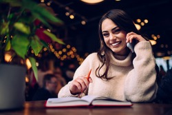 Smiling brunette female with orange pen and planner resting in cafe with illumination behind while laughing and talking on cellphone