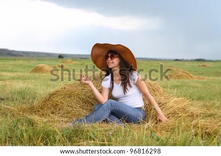 Smiling brunette girl in hat in summer day