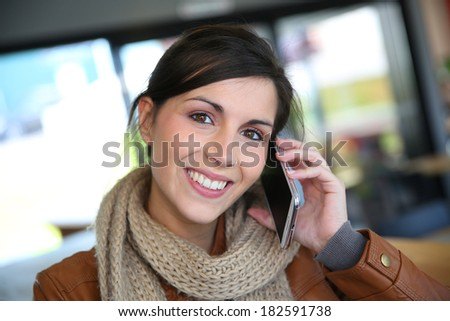 Smiling brunette girl using smartphone in coffee shop