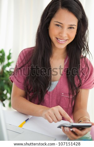 Smiling brunette student using a calculator to do her homework