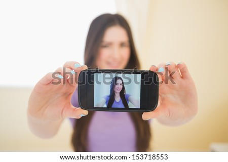Smiling brunette taking a photo of herself with her mobile phone in a bedroom