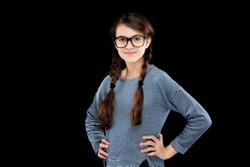 Smiling brunette teen girl wearing glasses isolated on black