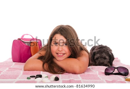 smiling brunette teenage girl in swimsuit at the beach with her shipoo dog (studio setting with beach and personal items) isolated on white background