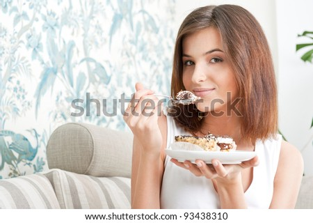 Smiling brunette woman eating some cake in the living room in her apartment