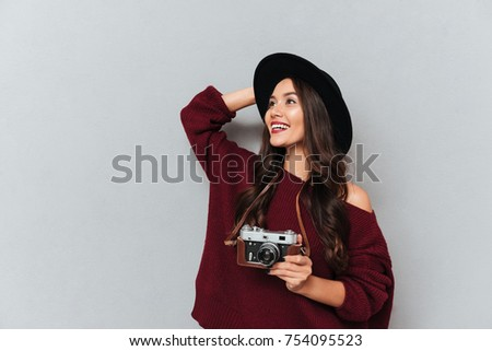 Smiling brunette woman in sweater and hat holding retro camera while looking away over gray background #754095523
