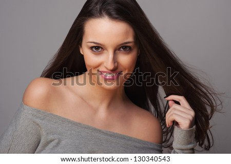 Smiling brunette woman intense close up portrait on grey background.