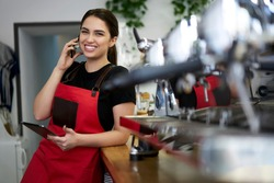 Smiling brunette woman waitress in uniform enjoying conversation on mobile phone making banking at work, prosperous female owner of coffee house calling to operator making order for retail business