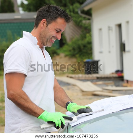 Smiling builder consulting blueprint Smiling builder standing in front of a new build house consulting a blueprint on the bonnet of his car