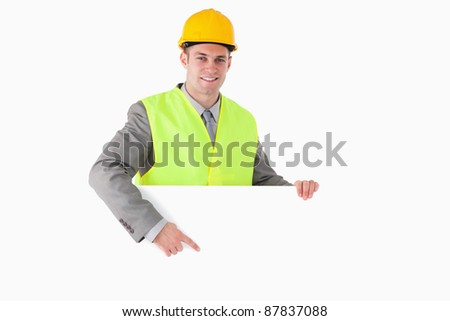 Smiling builder pointing at something against a white background