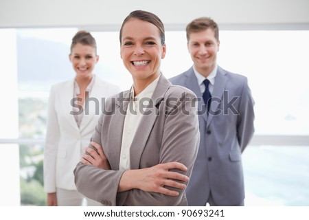 Smiling business consultant with arms folded together with her team