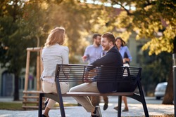 Smiling business man and woman sitting at bench at park and talking.