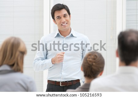 Smiling business man have a speech at business presentation