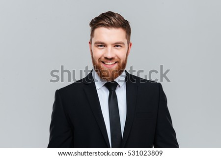 Smiling business man in black suit with tie in studio looking at camera. Isolated gray background #531023809