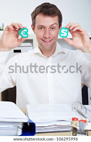 Smiling business man in office holding Dollar and Euro signs